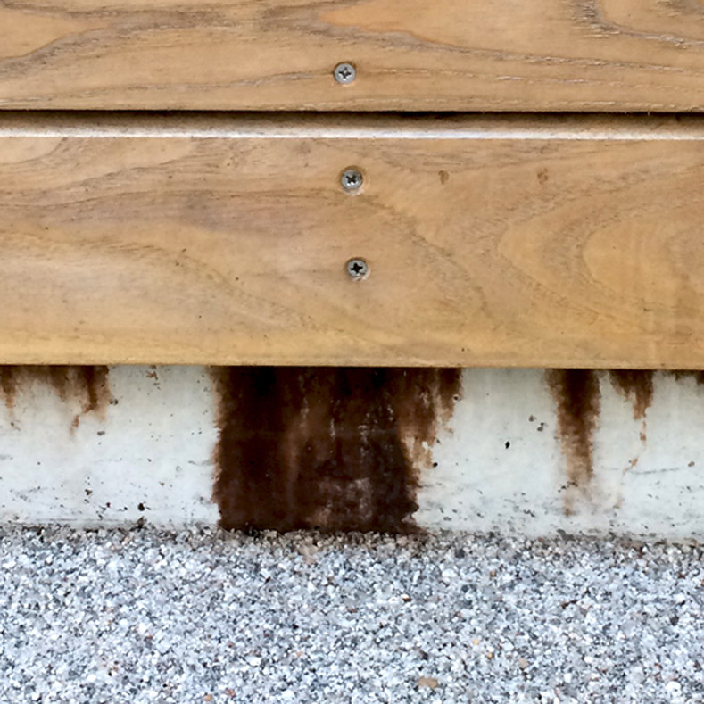 Rust coloured tannin leaching from timber cladding onto concrete below lo